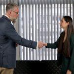 Ein Mann verabschiedet sich per Handschlag von der Chefin nach einer ordentlichen Kündigung