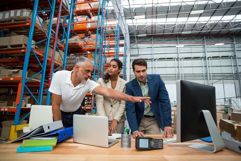 Ein Chef in der Werkhalle hat die Fürsorgepflicht und analysiert die Einhaltung der Arbeitsvorschriften