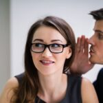 Ein Mann flüstert einer Frau ein Teil der Gerüchteküche ins Ohr