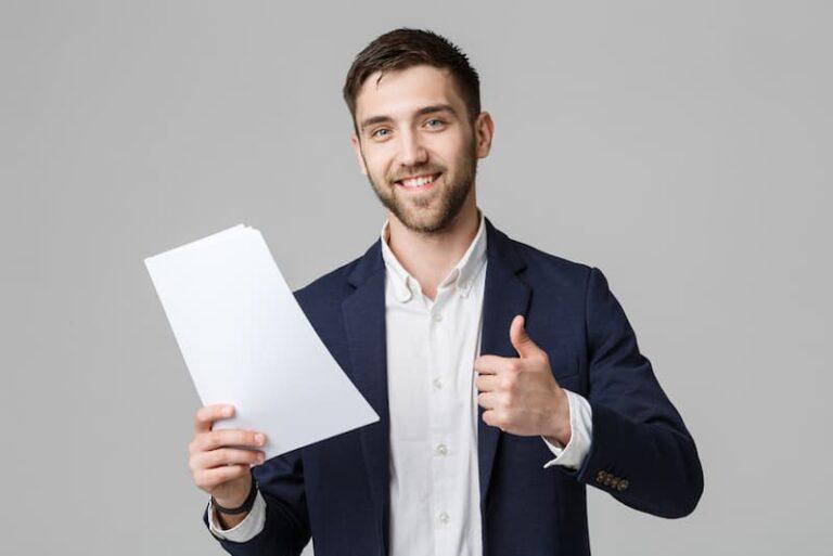 Ein junger Mann hält sein Zwischenzeugnis in der Hand