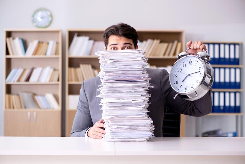Ein Mann sitzt vor einem Papierhaufen, er hat ein schlechtes Zeitmanagement