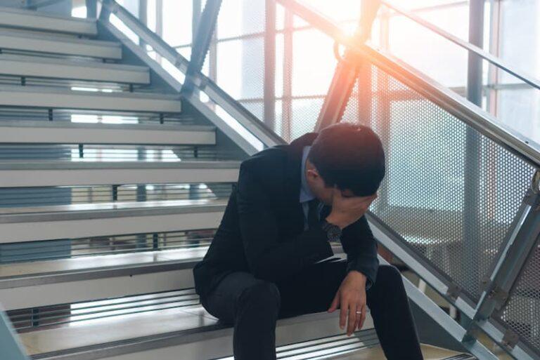 Ein Mann sitzt auf einer Treppe nach seiner Freistellung