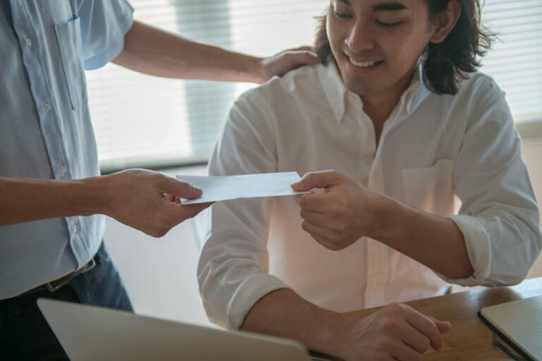 Ein Mann erhält eine Bonuszahlung in einem Umschlag