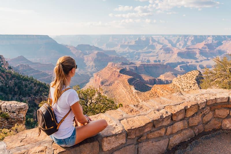 Eine Frau sitzt am Grand Canyon und macht ein Sabbatical