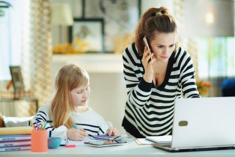 Eine Frau arbeitet am Laptop und das Kind spielt daneben, eine Doppelbelastung