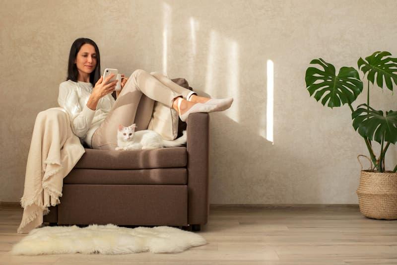 Eine Frau sitzt im Stuhl und lebt nach dem Konzept des Frugalismus