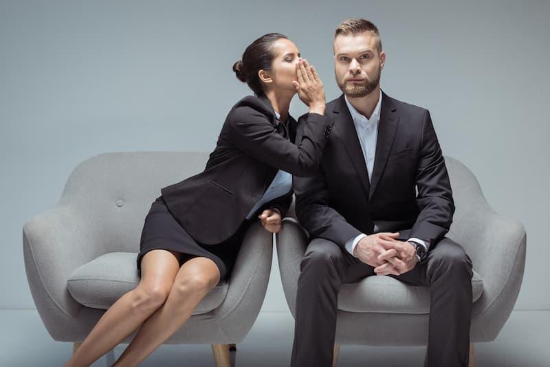 Eine Frau flüstert einem Mann ein Betriebsgeheimnis ins Ohr
