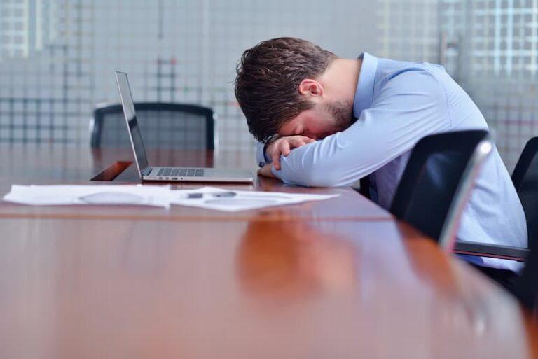 Ein Mann senkt den Kopf auf die Arme, er erleidet Mobbing am Arbeitsplatz