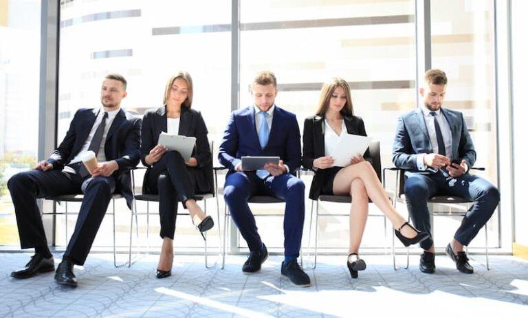 Mehrere Personen sitzen in einer Reihe vor einem Jobinterview