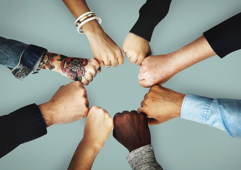Menschen halten ihre Fäuste zusammen, ein Symbol für Teamwork
