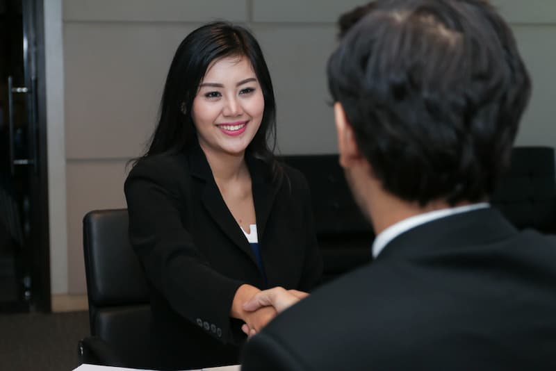Ein Mann erhält von der Chefin eine Gehaltserhöhung und schüttelt die Hand