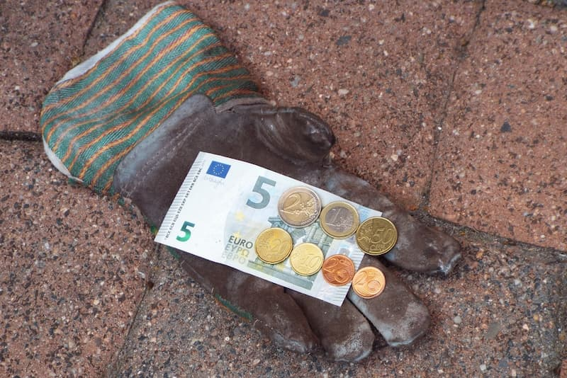 Ein Arbeitshandschuh mit Geldmünzen und einem Euroschein, Symboldbild für den Mindestlohn