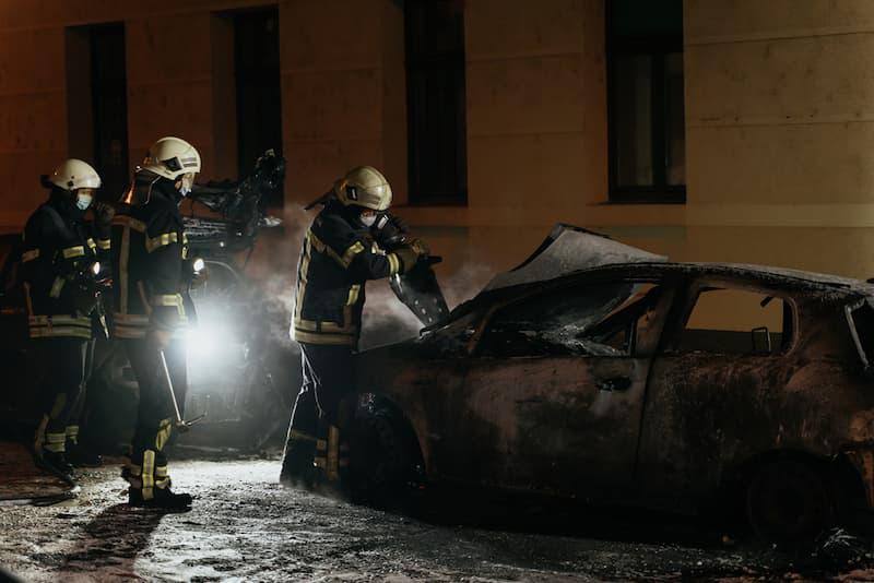 Feuerwehrmänner bei der Nachtarbeit, sie löschen ein Auto