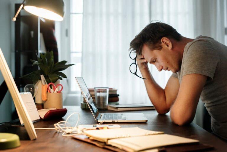 Ein Mann sitzt vor dem Laptop und hält sich die Stirn, er hat Bewerbungsangst