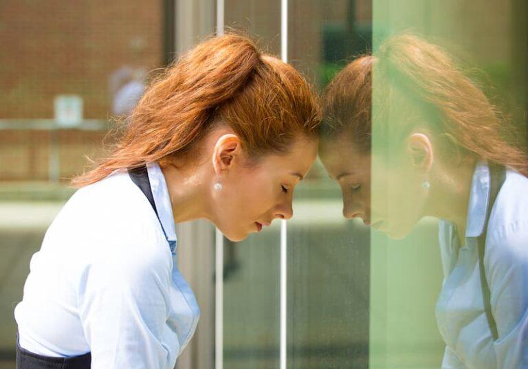 Eine Frau lehnt mit dem Kopf an einer Scheibe und übt Selbstkritik