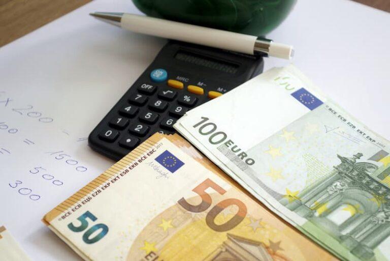 Mehrere Geldscheine und Taschenrechner als Symbolbild für den Sonntagszuschlag
