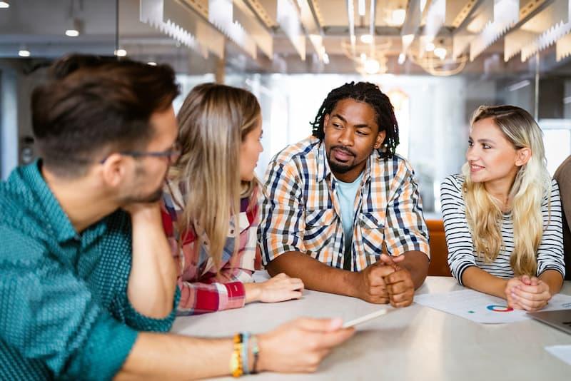 Mitarbeiter in einem Team diskutieren, sie haben alle eine hohe soziale Kompetenz