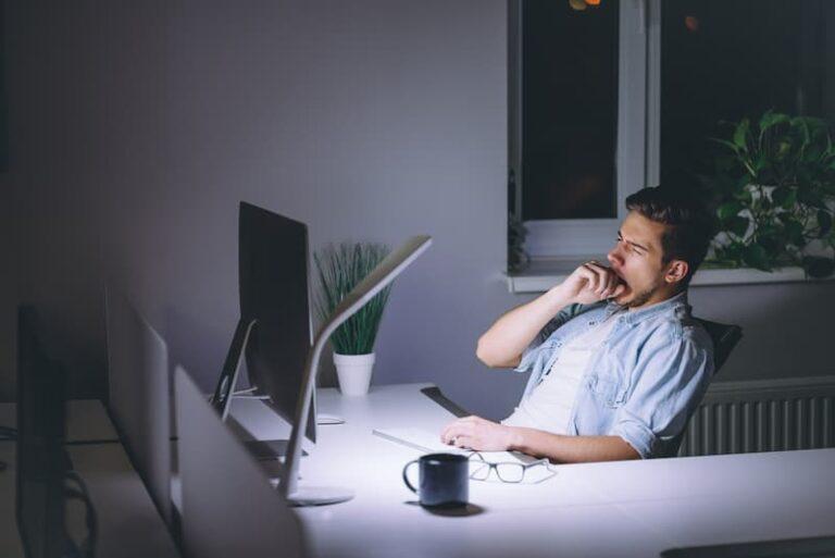 Ein Mann arbeitet abends im Büro, er erhält einen Überstundenausgleich