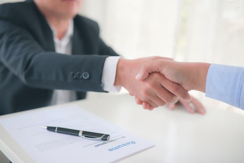 Ein Mann unterschreibt einen Arbeitsvertrag, aus diesem ergeben sich Pflichtverletzungen am Arbeitsplatz