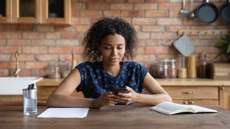 Eine Frau hat einen Job auf Abruf und sitzt Zuhause am Küchentisch