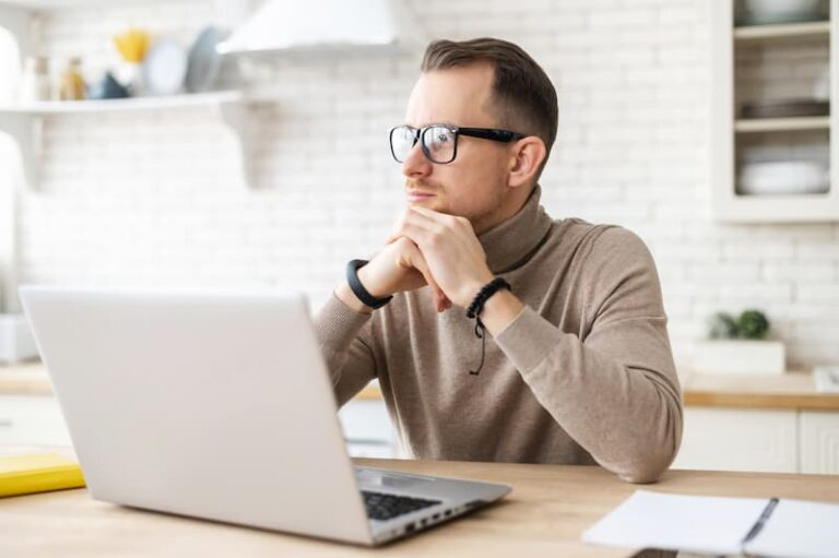 Ein Mann sitzt am Laptop und ist nachdenklich nach einigen Bewerbungs- und Job-Absagen