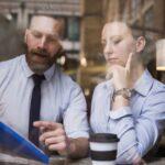 Ein Mann versucht in einem Gespräch mit einer Kollegin richtig zu kritisieren und konstruktive Kritik anzubringen