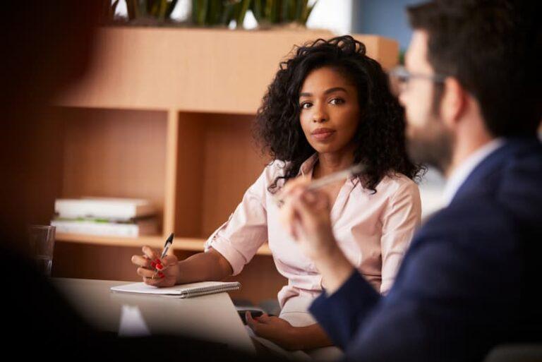 Eine Frau schreibt im Meeting ein Protokoll