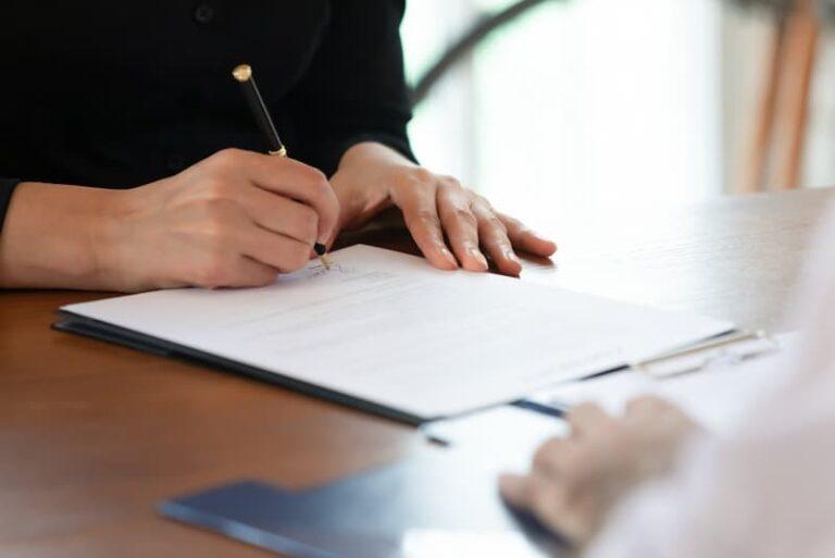 Eine Frau unterschreibt einen Arbeitsvertrag, was muss in diesem stehen?